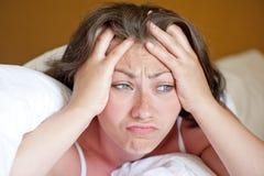 女孩早晨在床上醒了在一种坏心情 库存照片