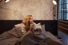 女孩早晨饮料咖啡在床上 清早,太阳未上升  免版税库存图片