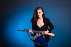 女孩时尚摄影在有枪的演播室是危险的 免版税库存照片
