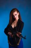 女孩时尚摄影在有枪的演播室是危险的 图库摄影