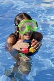 女孩是与颜色球的游泳池 免版税库存图片