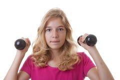 女孩是体育与在白色背景的哑铃 免版税图库摄影