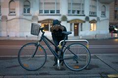 女孩是公园她的沿街道的自行车 库存照片