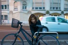 女孩是公园她的沿街道的自行车 免版税图库摄影