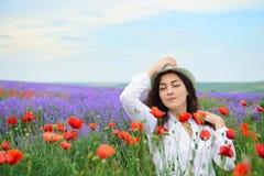 女孩是在与红色鸦片花的淡紫色领域,美好的夏天风景 免版税库存图片