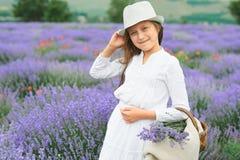 女孩是在淡紫色领域,美丽的画象,白色礼服,夏天风景 免版税库存照片