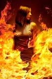 女孩是在燃烧的火焰 库存照片