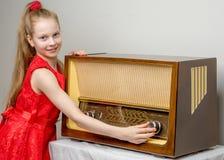 女孩是在老收音机 图库摄影