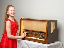 女孩是在老收音机 免版税库存图片