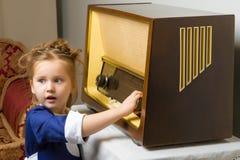 女孩是在老收音机 库存照片