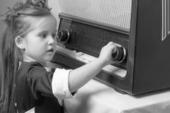 女孩是在老收音机 免版税图库摄影