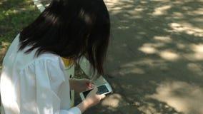 女孩是在闲谈,写,并且读书评论到新的岗位对手机被连接到互联网,当坐时 股票视频