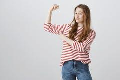 女孩是坚强和强有力的 举有握紧拳头的确信的相当白种人女孩画象胳膊,显示 免版税库存照片