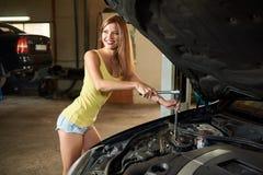 女孩是夹具,当修理有开放敞篷的时汽车 库存照片