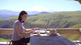 女孩是工作在膝上型计算机和喝从在山背景的一个杯子的自由职业者  股票录像