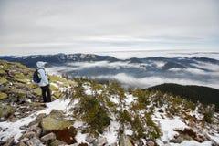女孩是有一个背包的一个游人在积雪的山背景中  库存照片