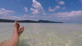 女孩是松弛在海 海和腿的美丽的景色 股票视频