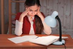女孩是非常疲乏做家庭作业 免版税库存图片