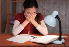 女孩是非常疲乏执行家庭作业 库存图片