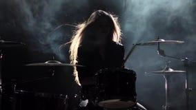 女孩是从演奏鼓的解雇,演奏精力充沛的音乐 黑烟背景 剪影 慢的行动 股票视频
