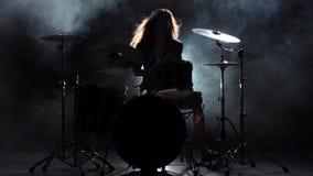女孩是从演奏鼓的解雇,演奏精力充沛的音乐 黑烟背景 剪影 慢的行动 股票录像