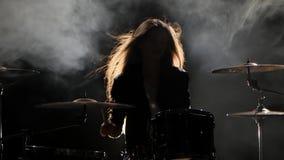 女孩是从演奏鼓的解雇,演奏精力充沛的音乐 黑烟背景 剪影 股票录像