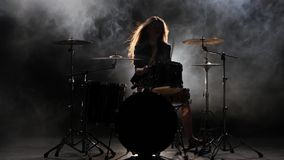 女孩是从演奏鼓的解雇,演奏精力充沛的音乐 黑烟背景 剪影 股票视频