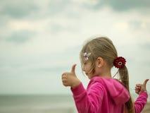 女孩显示她手所有是好与在冷的海的岸的生活 库存图片