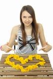 女孩显示野花的心脏。黄色蒲公英的心脏。 免版税库存照片