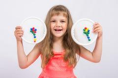 女孩显示从马赛克收集的五颜六色的花 免版税库存照片
