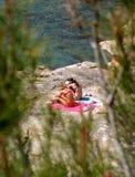 女孩晒日光浴岩石的海运二个年轻人 免版税库存照片