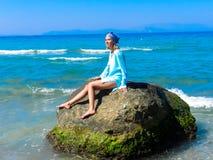 女孩晒日光浴在一块大石头的海边 库存照片