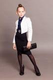 女孩有一个袋子的企业夫人在灰色背景 免版税库存照片