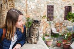 女孩有与一只地方猫的一次好的谈话在意大利 免版税图库摄影