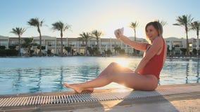 女孩有与手机的乐趣照相在水池附近 做selfies的红色时兴的比基尼泳装游泳衣的性感的妇女 股票视频