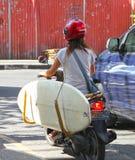 女孩有冲浪板的骑马摩托车 免版税库存图片