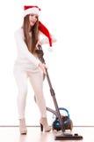 女孩有吸尘器的圣诞老人帽子 免版税库存照片