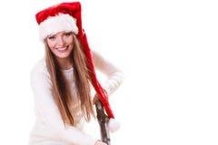 女孩有吸尘器的圣诞老人帽子 库存照片