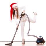 女孩有吸尘器的圣诞老人帽子 图库摄影