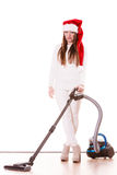 女孩有吸尘器的圣诞老人帽子 免版税库存图片