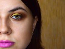女孩有嫉妒的构成在黄色和金子口气 在嘴唇上有一支桃红色唇膏 免版税库存图片
