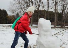 女孩有效地雕刻雪人 免版税库存照片