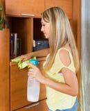 女孩有清洁剂和旧布的清洁家具 图库摄影