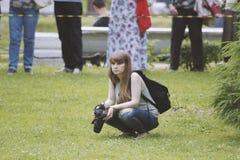 女孩有照相机的摄影师在有思想性 图库摄影