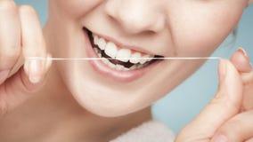 女孩有牙线的清洁牙。医疗保健 免版税图库摄影