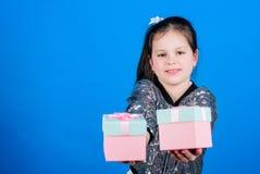女孩有礼物盒蓝色背景 r o 逗人喜爱的孩子运载礼物盒   免版税库存图片