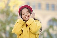 女孩有耳机都市背景 音乐的正面影响 儿童女孩享受音乐的法式成套装备 免版税库存图片