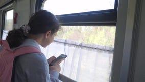女孩有背包的少年旅客支持列车车箱的窗口有智能手机的 旅行运输 影视素材