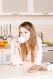 女孩有长的流动的头发的一件白人的衬衣喝着茶在桌上的厨房手肘 早晨 库存图片