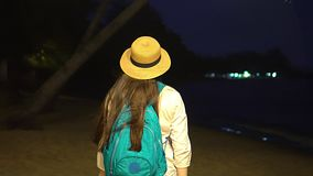 女孩有长的黑发的和草帽的在海滩以后去在晚上点燃照明 2th混淆女孩岁月 股票录像